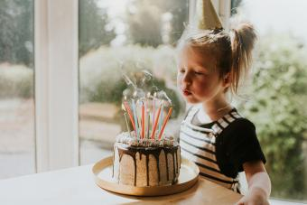 Birthday girl blowing out the candles on her cake