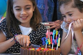Birthday girl cutting a birthday party cake