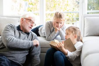 Two girls and grandfather reading book in living room