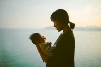 Mother hugging baby girl at home in front of window