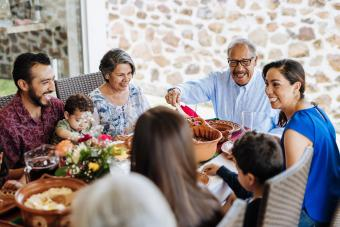 Latin senior man serving the food to his family at dinner table