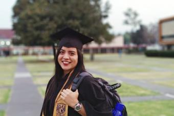 Smiling Woman In Graduation Gown Standing On Field Campus