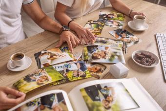 Married couple look at their printed wedding photos spread across the table