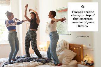 Cheerful young women dancing on bed at home
