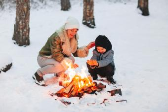 Mother And Son In Snow During Winter With Bonfire