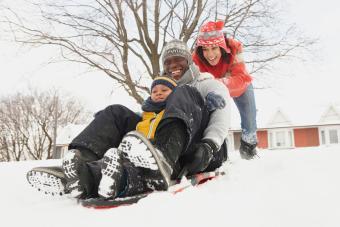 Black family sledding in snow