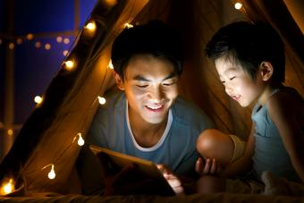 Father and son in a tent using tablet together