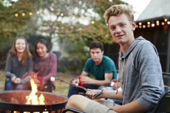 teenagers roasting marshmallow around fire pit