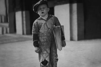 young newsboy stands on the sidewalk selling newspapers 1925