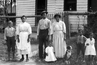 Black family stands in front of their home 1920s
