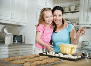 young girl making cookies with mom