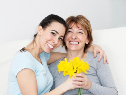 Daughter giving flowers to mother