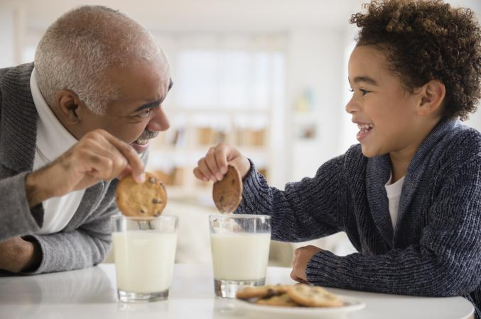 Grandfather and grandson eating cookies