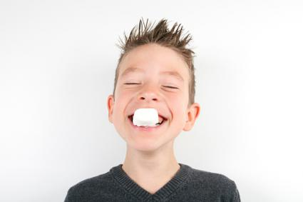 Boy holding marshmallow in his teeth