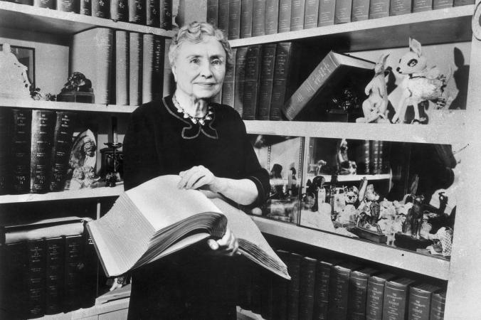 Helen Keller holding a Braille volume