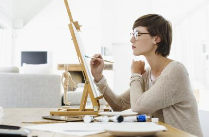 Woman painting on easel at table