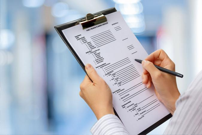 Woman using family reunion planning checklist