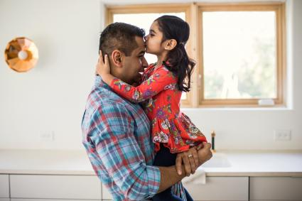 Daughter kissing father at home