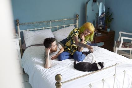 Young hipster couple lying on their bed together playing with their pet cat