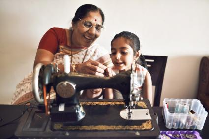Senior woman working on sewing machine along with granddaughter
