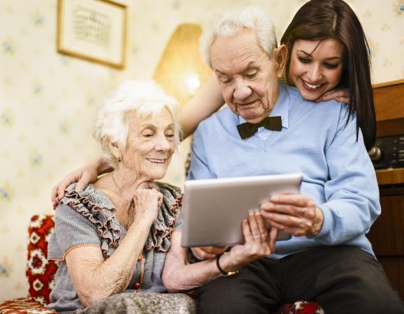 Grandparents and granddaughter reading poem on tablet