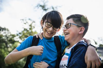 School age cousins laughing outdoors