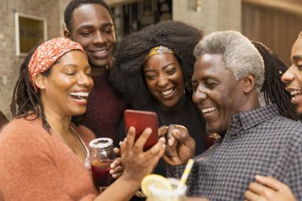 Happy multi-generation family using smart phone