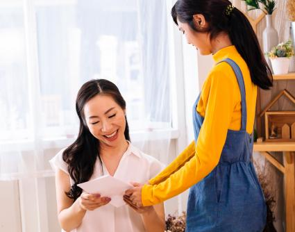 Smiling Asian mother and daughter with card