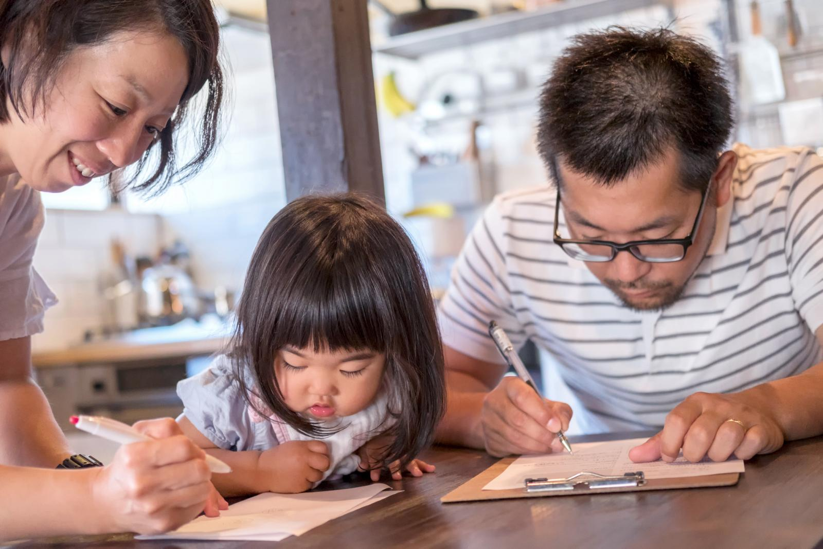 Husband and Wife Fill Out Paperwork While Young Daughter Watches