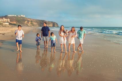 Large blended family walking on beach