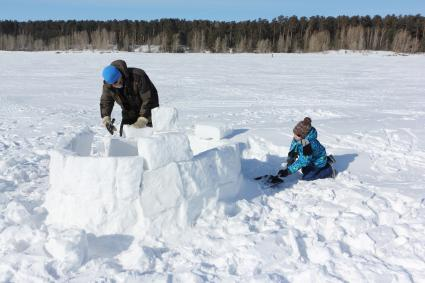 Man and boy building igloo