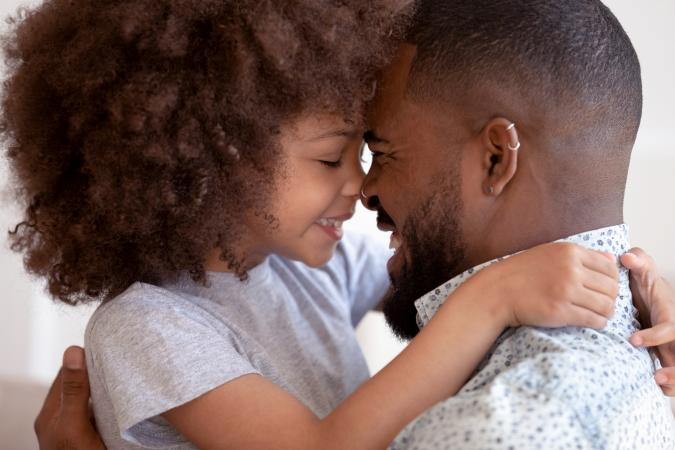 Cute daughter embraces and touch noses with happy dad