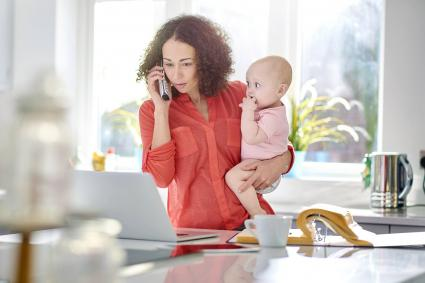 Woman in her kitchen holding a baby while talking on the phone