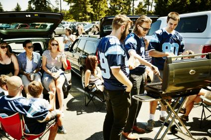 Friends barbecuing during tailgating party in football stadium parking lot