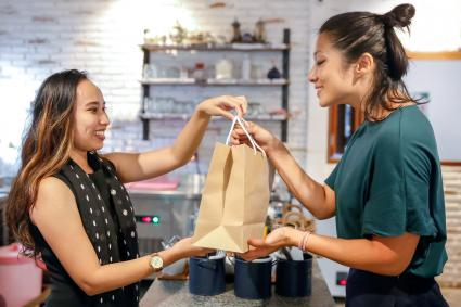 Customer talking leftovers home in brown paper bag