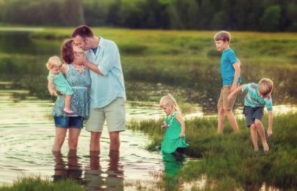 Family of six wading in water