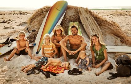 Family sitting on the beach with surf boards