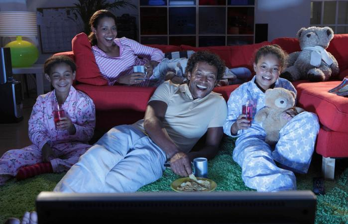 Family watching TV and laughing