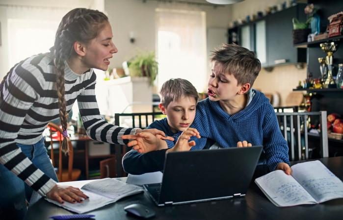 Three kids fighting for laptop at home