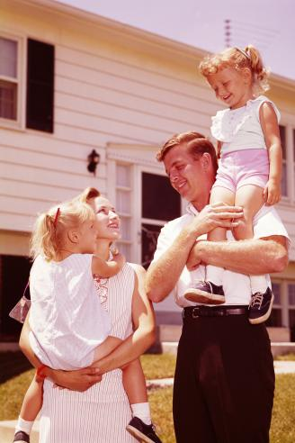 Family outside suburban home in the 1960s