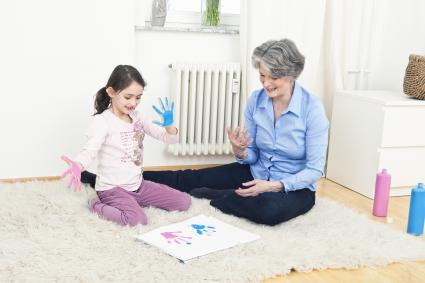 Grandmother and granddaughter finger painting
