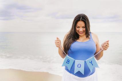 Pregnant woman holding boy banner on beach