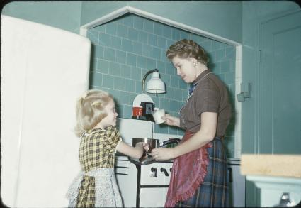 1950s mother teaching her daughter how to cook