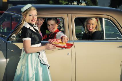 1950s car hop at drive-in restaurant with teenage customers