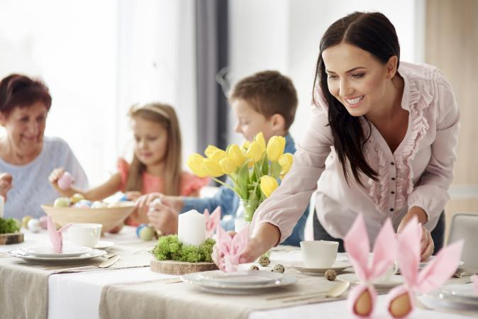 Family preparing place settings at easter dining table