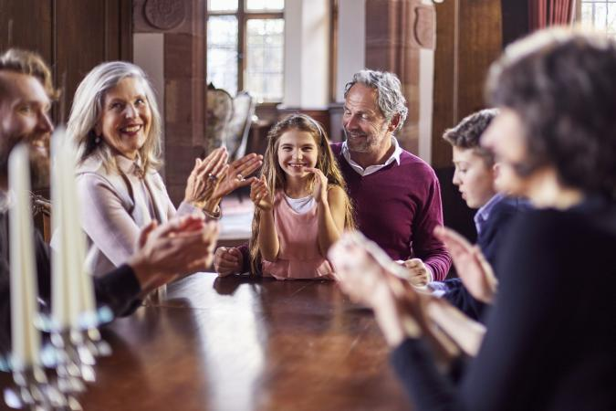 Happy family sitting around wooden table applauding