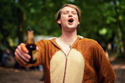 Man wearing animal costume holding beer bottle