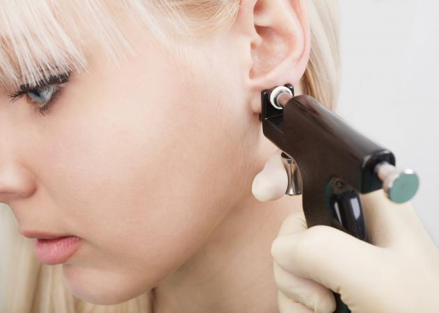Woman having ears pierced