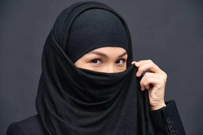 Woman holding chador over face