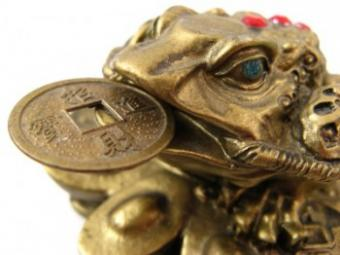 Three-legged toad with coin in mouth.